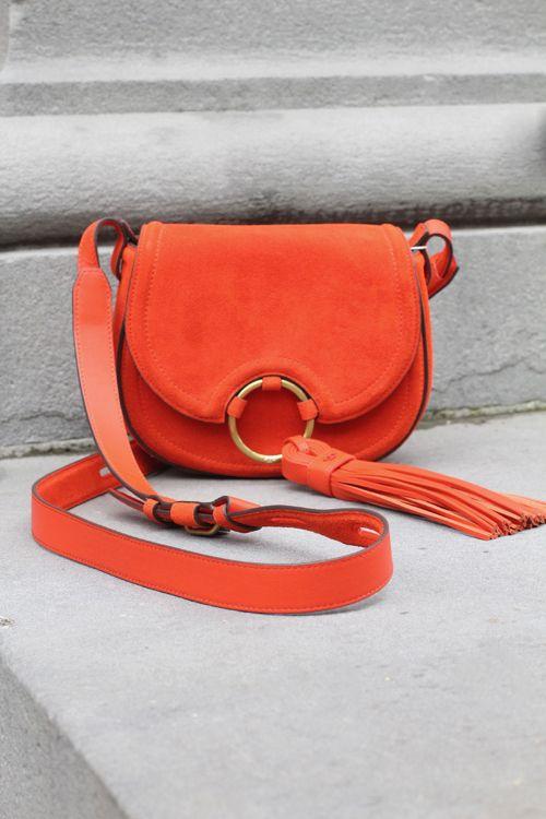 Tassel Mini Saddle Bag fra Tory Burch er en mellomstor, veske i orange, semsketskinn. Vesken har ett stort hovedrom, samt to praktiskeinnerlommer. Vesken lukkes med magnetlås og skulderstroppen er regulerbar. Avtagbartassel. Leveres med støvpose. Høyde 17 cm. Vidde 20cm. Laget av 100% skinn.