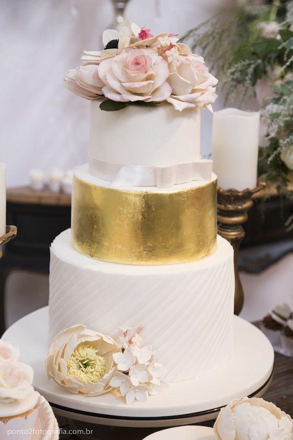 Bolo Dolce Fabricca  Com andares brancos e em folha dourada comestível e flor de açúcar no topo.
