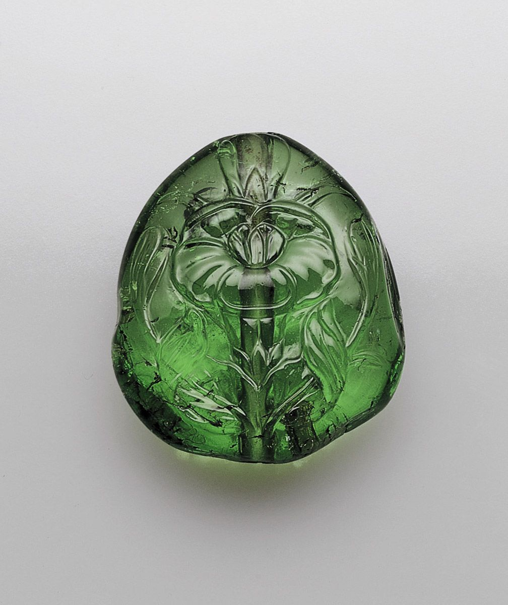 Relief carved emerald drilled longitudinally for