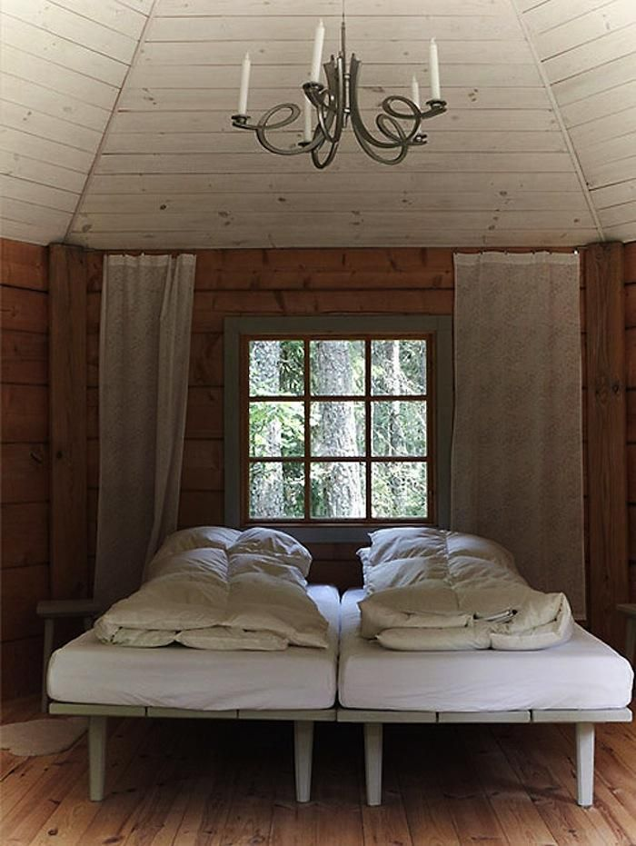 Urnatur Cabins in Sweden Simple Cottage Twin Beds White Bedding Wrought Iron Chandelier