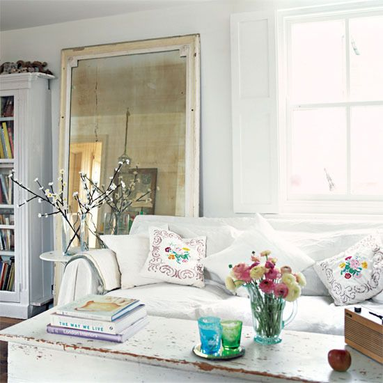 white cottage living room with leaning mirror