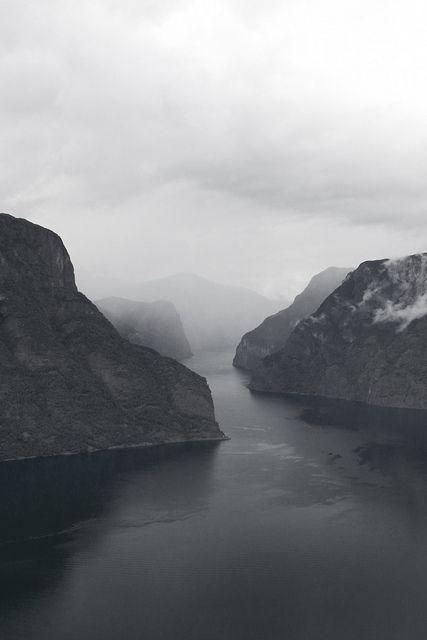 Selv under de lave skyene og over den mørke, dype fjorden ser man skjønnheten i det dramatiske landskapet