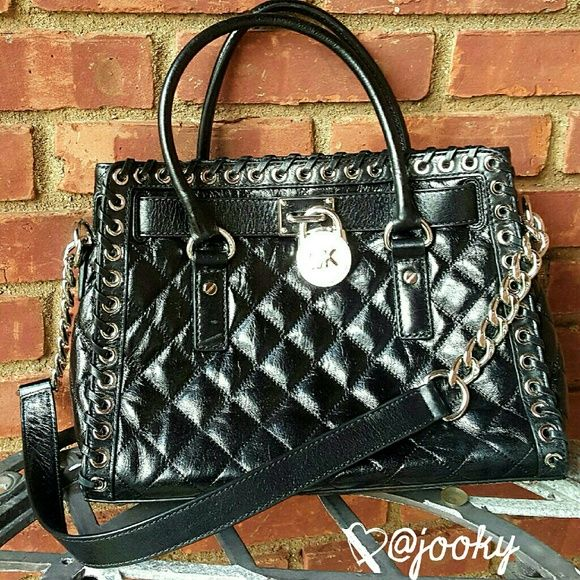 """MICHAEL KORS Hippie Grommet Hamilton gorgeous black quilted leather Hippie Grommet Hamilton satchel. silver hardware. has MK lock on front as decor, but is an actual functional lock, 0key included! both straps are attached. long one is 1/2 black leather, 1/2 metal chamin. medium sized, roomy, magnetic snap closure. attached inside key fob. NWT. n5o trades.   leather silver hardware strap drops 5"""", 11"""" open width 10"""" height 9.5"""" bottom width 13"""" 1 zippered pouch inside 2 open pouches inside…"""
