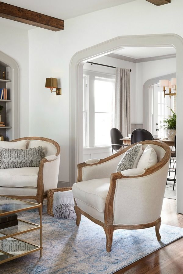 Come get inspired by Tranquil and Timeless Tudor Design Details From a Serene 1920s Texas Cottage renovated on HGTV's Fixer Upper by Chip and Joanna and known as the Scrivano House. #fixerupper #scrivano #cottagestyle #interiordesign #greytrim #serenedecor# livingroom #barrelchair