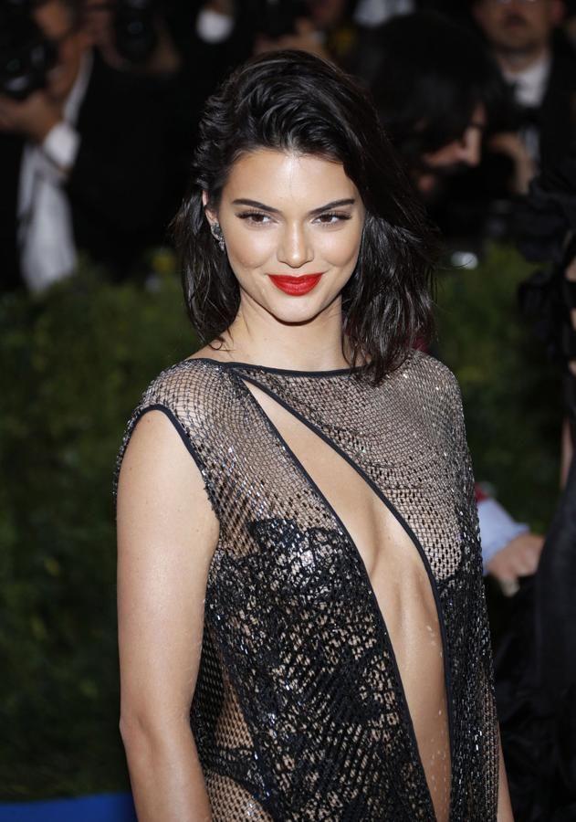 ccdace6d80 La modelo Kendall Jenner combina los labios rojos con un discreto  maquillaje y un peinado con efecto mojado. Un look perfecto para las noches  de verano.