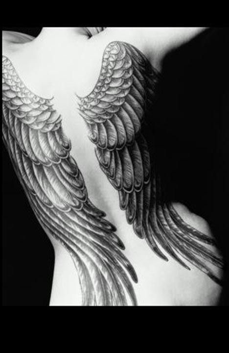 Tattoo of wings, possibly inspired by renaissance paintings of angels, on a woman's back.