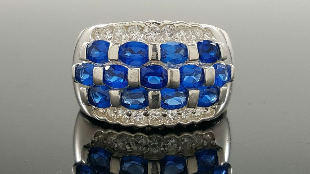 """There are some minor scratches and other marks on the ring.<br/><br/>Featured here is an elegant sterling silver ring with 15 oval blue jadeite and 18 round cut CZ settings. Stones: Blue Jadeite, CZ. Shank Dimension: ½"""". Cut: Oval, Round. Metal: Sterling Silver. Top Dimension: ¾"""". 