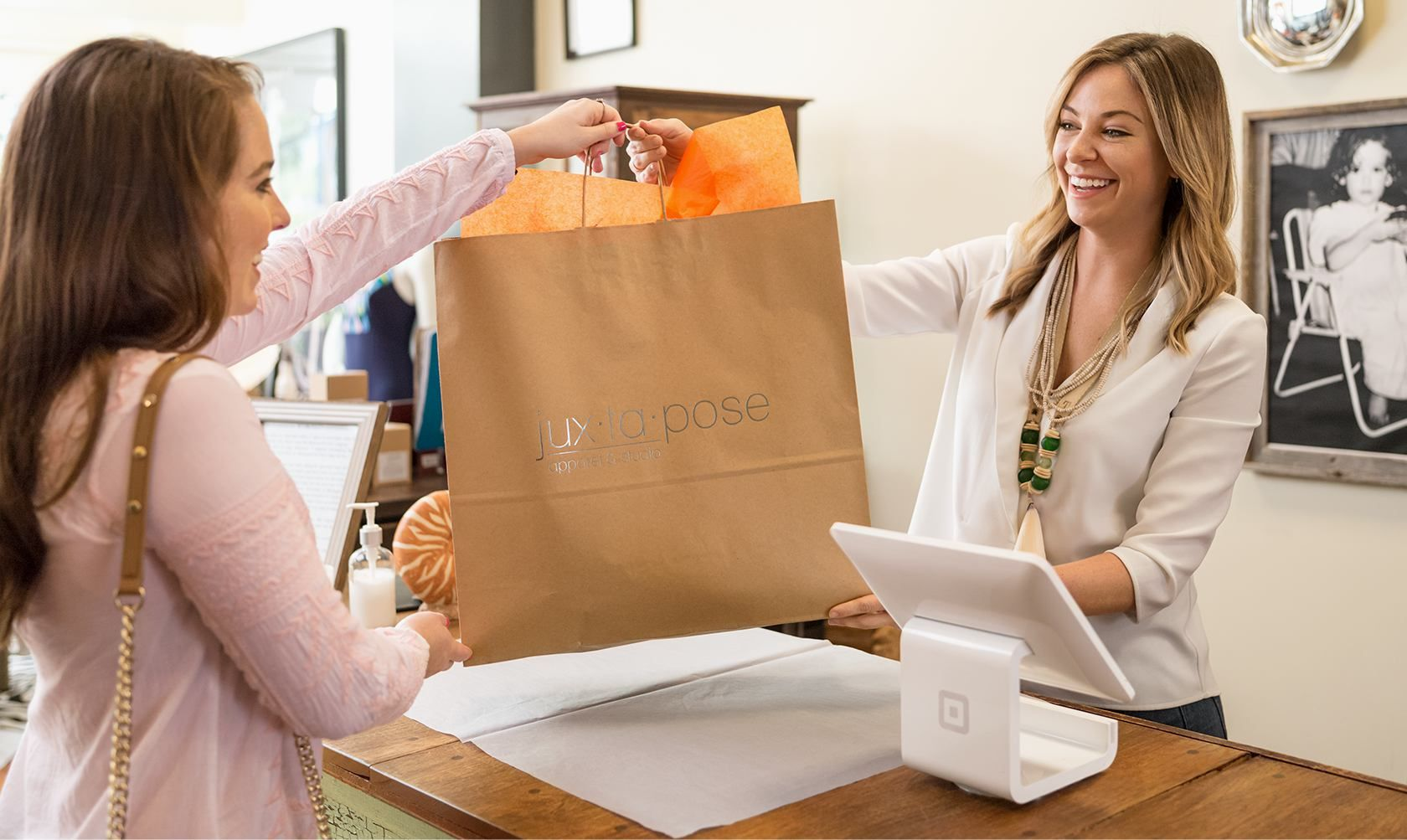 A woman customer being handed a shopping bag at the