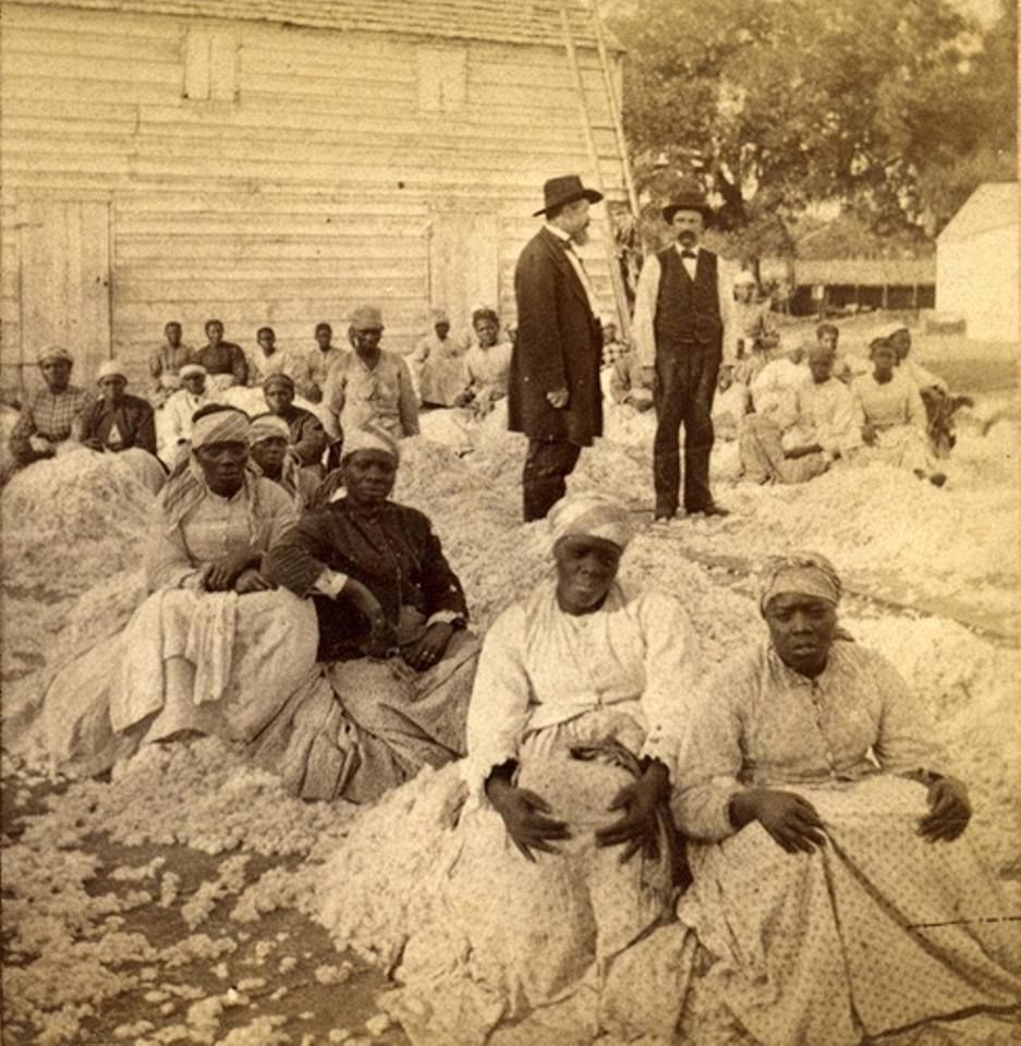 """A rare photograph of a group of women sitting on piles of cotton with two white male overseers. Entitled """"Freedom on the Plantation"""" circa 1863-1866. Robin Stanford Collection, DeGolyer Library, Southern Methodist University."""