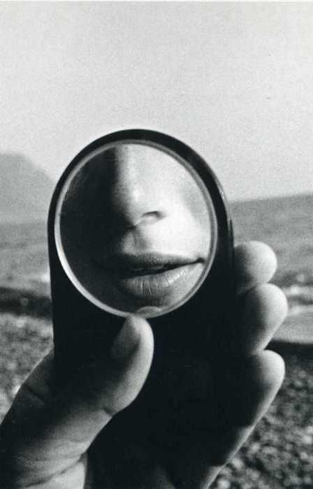 Reflected nose & mouth in small mirror w/ llarge landscape background: Photo by Ralph Gibson