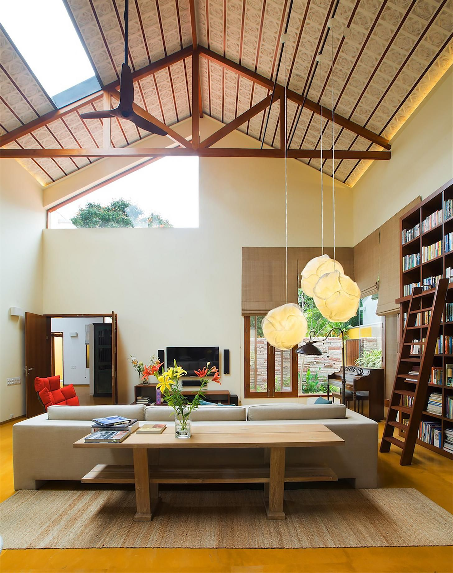 Brightly Lit Living Room Under A Vaulted Ceiling With A Bookshelf Wall, Bangalore, Karnataka