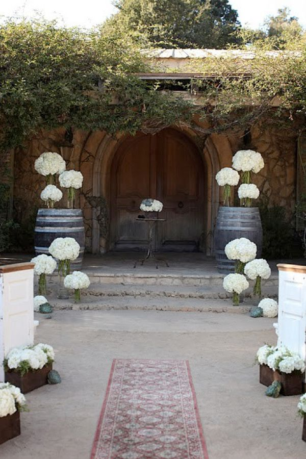 Wine barrels topped with flowers on each side of the altar for Altar decoration wedding
