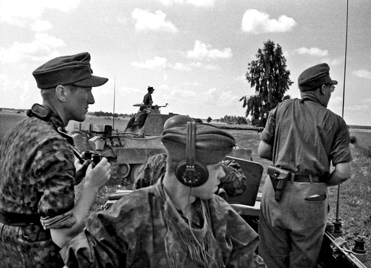 All eyes towards the front! The view from an Sd.Kfz. 251/3 Ausf.D of the Wiking Division, Wilanowo area in July 1944. On the right is SS-Sturmbannführer Paul Kümmel, battalion commander in SS-Panzer Regiment 5 and on the left is probably SS-Hauptsturmführer Paul Scholven from SS-Panzergrenadier Regiment 9 Germania.