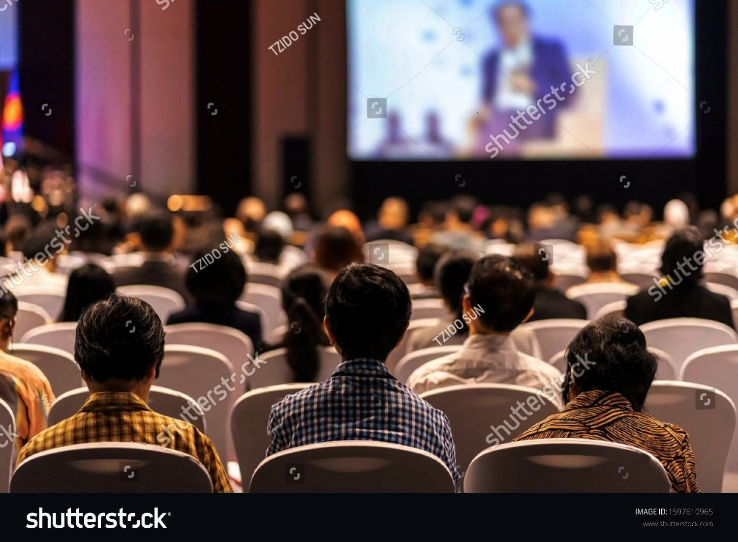 Audience listening Speakers on the stage in the conference hall or seminar meeting business and education about investment concept Rear view of Audience listening Speaker...