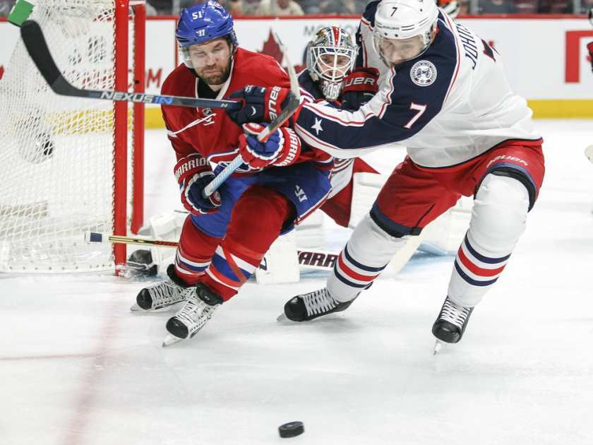 Montreal Canadiens David Desharnais, left, fights for loose puck with Columbus Blue Jackets Jack Johnson during first period of National Hockey League game in Montreal Tuesday December 1, 2015. Blue Jackets goalie Sergei Bobrovsky watches from the net.