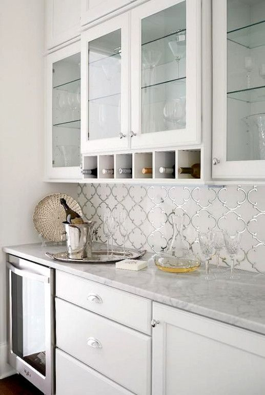 White butler's pantry boasts glass-front upper cabinets ...