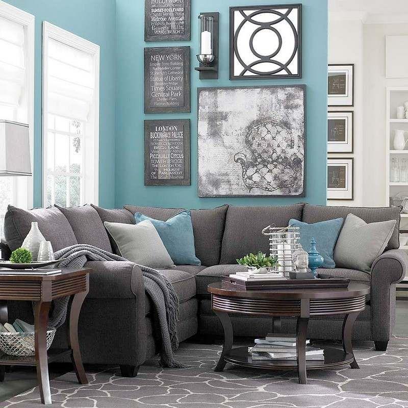peinture murale bleu turquoise clair en contraste avec le canape gris et le tapis gris a motifs blancs