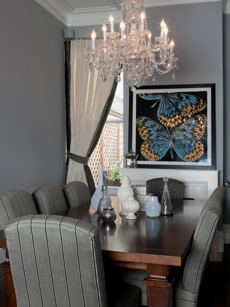 A small gray dining room combines the masculine and feminine with menswear-striped chairs and a crystal chandelier.
