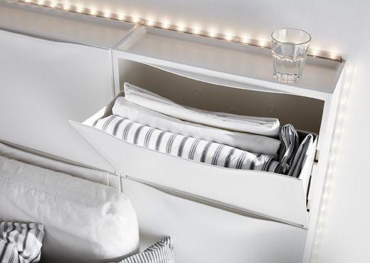 Šesť bielych skriniek na topánky IKEA TRONES tvoria čelo postele.