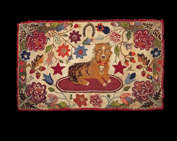 Folky dog on an oval mat with colorful stars, florals, and a good-luck horseshoe.    New England, circa 1860    Mounted, 32 x 52 inches
