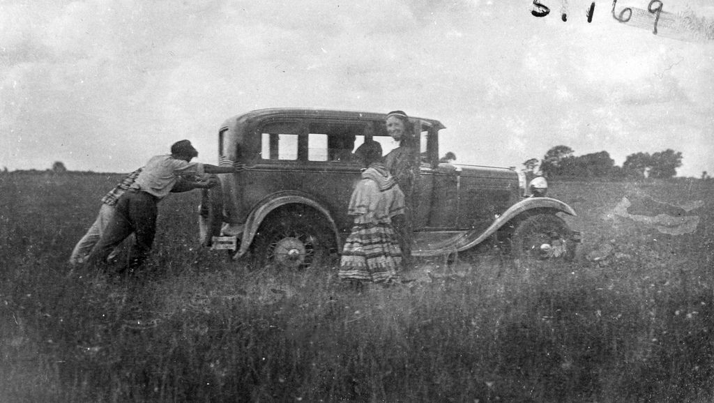 Deaconess Bedell watching the Miccosukee pushing her stuck Model A | by State Library and Archives of Florida. Date: Between 1933 and 1960.