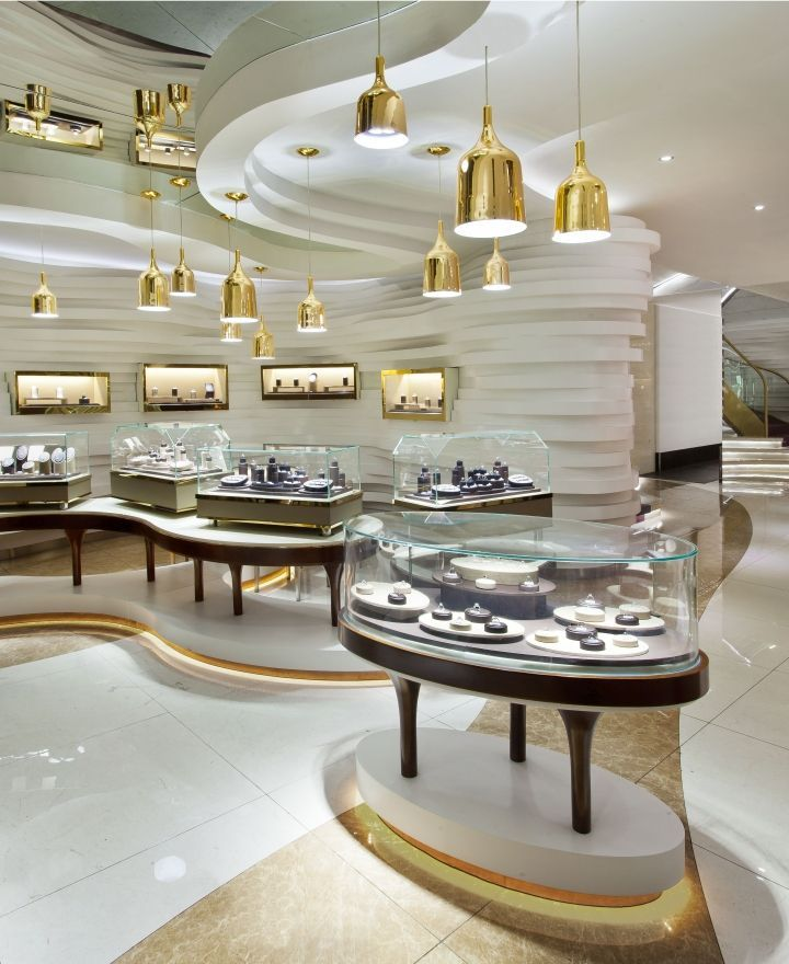 Gold and bold soft lines create depth within the space for Jewellery showrooms interior designs