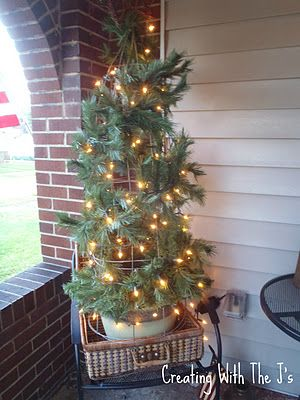Tomato cage tree - I used evergreen garland from Dollar General, added silk  poinsettias and lights, oh, and a bow on top - Tomato Cage Tree - I Used Evergreen Garland From Dollar General