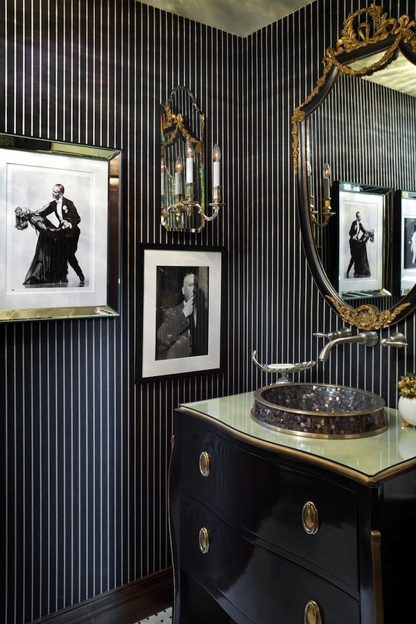 Powder Room, pinstripes on the wall create a slightly masculine backdrop for this glossy black chest turned powder room sink vanity. Black and white photos in mismatched frames dwell companionably with ornate wall sconces and mirror. It's an altogether elegant look.