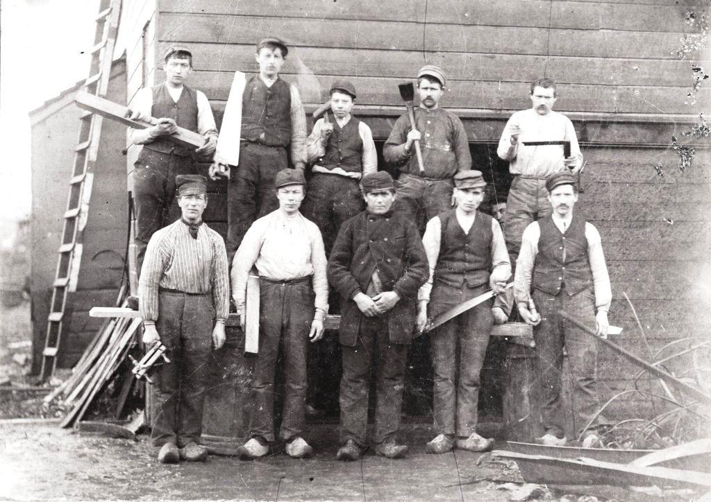 Deze foto is omstreeks 1900 gemaakt. We zien hier Adrianus Ruijtenberg staande tussen zijn scheepmakerknechts. Bovenste rij vlnr: Cornelis Fijneman  ...