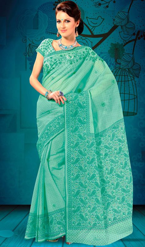 Turquoise Green Cotton Embroidered Printed Saree Beautify yourself draped in this turquoise green shade cotton saree. Saree is beautifully accentuated with printed and embroidered decorative patterns that gives you a pretty look. Comes with a matching stitched round neck blouse with 6 inches sleeves. #CottonEmbroideredPrintedSaree #LadiesDesignerSarees