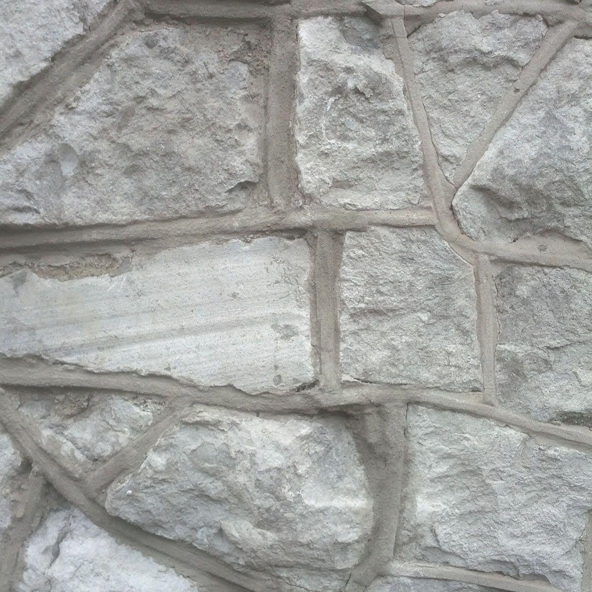 De structuur van de stenen muur is ruw en hard. Enkele stenen steken meer uit de stenen muur waardoor er een waar reliëf ontstaat die de textuur mee vormt. De voegen zijn hoekig en hard en verbinden de stenen met elkaar.
