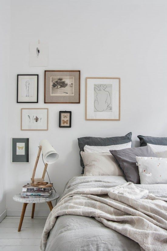spare - no headboard. simple linens, low circular side table. simplistic artwork - white walls. peaceful.