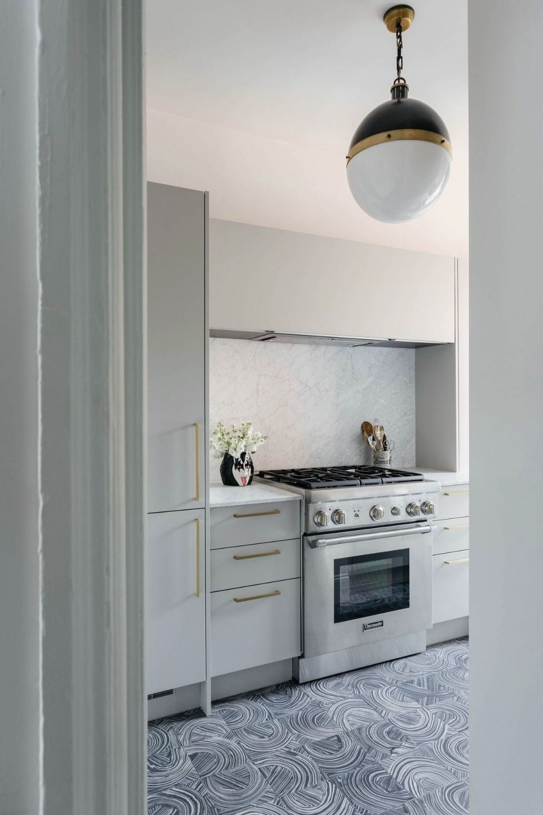 The swirly tiles are by Kelly Wearstler; the light is Thomas O'Brien's Hicks Pendant.  #Kitchen #KitchenRemodel #GutRemodel #Remodeling #Tiles #TileDesign #UrbanHomes #CustomKitchen #RenovatedKitchen #Renovating #RemodelKitchen #Stovetop #ModernKitchen #ModernDesign #ApartmentDesign #Lights #KitchenLights #AccentPiece #AccentLighting #Apartment #ApartmentDecor #Patterned #Floors