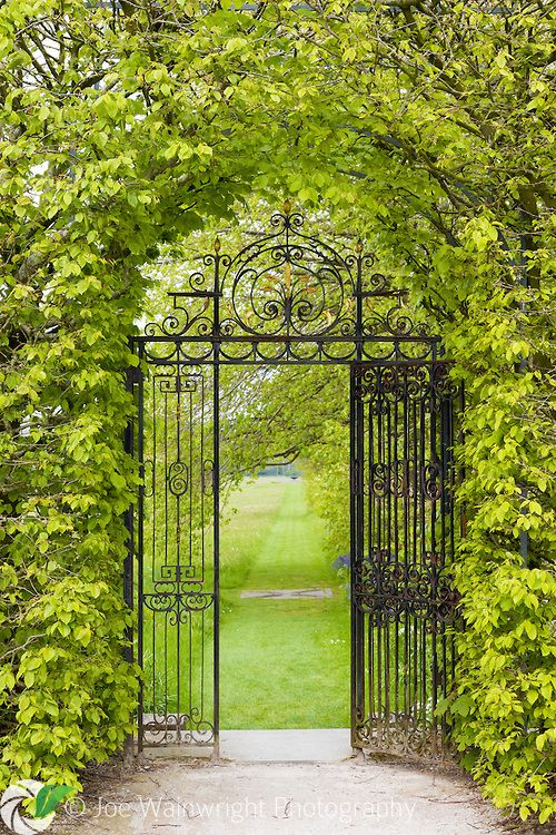 An ornate, wrought iron gate leads from the garden at Holker Hall, towards the wildflower meadow and sundial