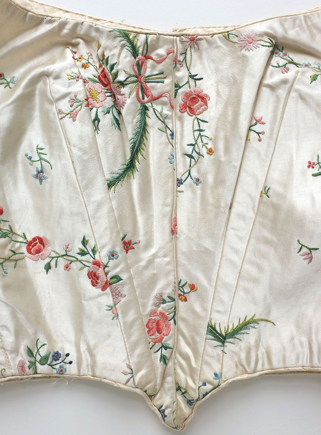 This is a beautiful mid 19th century dress bodice. Completely hand stitched with hand embroidered flowers on cream silk satin. Pleated detail to sleeves.  As fresh and colourful as the day it was made, this must have been carefully stored away for many years. Lined with cotton cambric. Fastens at the back with hooks and loops. Detail
