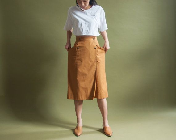 vintage 80s gaston jaunet mustard wrap skirt. large pockets that create shape. double breasted snap button closures. unlined. (1643t-1.0.8.B16)  materials: cotton poplin condition: excellent size: tag POLISH 42, equivalent to a US 10 (pinned at waist for fit)  waist: 31 hips: 41 length: 27.5   *measurements are taken seam to seam while lying flat. *doubled for bust, waist and hips. *model is a small, around 54   free U.S. shipping on orders over $150. reduced international shipping on…