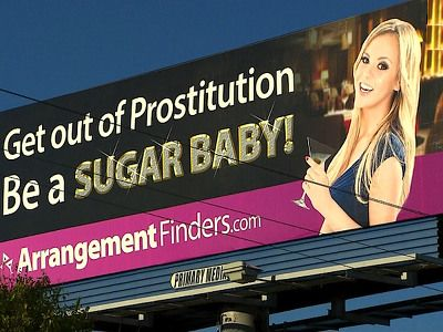 """A billboard in Texas pictures a young blond woman and the words, """"Get out of Prostitution.  Be a SUGAR BABY!""""  A """"sugar baby"""" is a woman who is paid by a man to have an ongoing sexual relationship with him.  Advocates say it's not prostitution, since it's not a one-time encounter.  Critics call it """"an online pimping service on a billboard."""" Whatever we call it, this is sexual exploitation.    (Photo Credit: CBSDFW.COM)"""