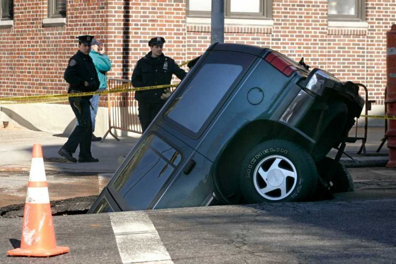 A sports utility vehicle is stuck in a sinkhole in the
