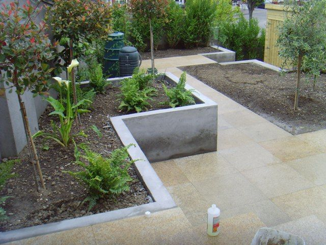Raised concrete planter bed matches level of steps Concrete planters
