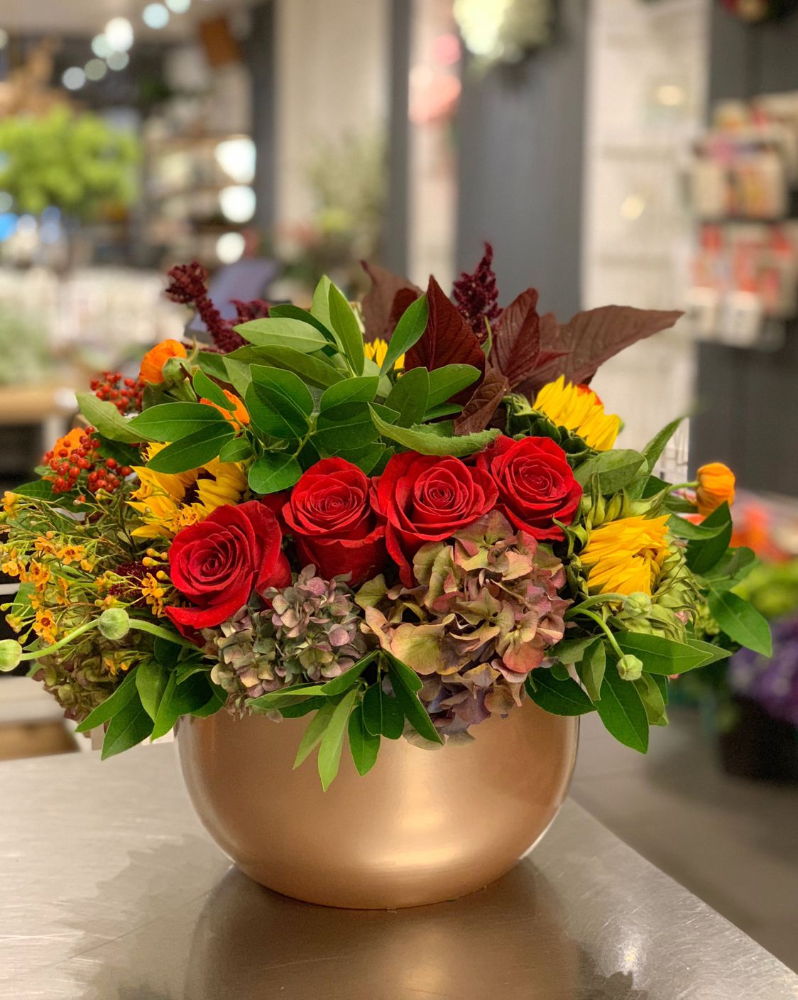 Red roses, sunflowers, celosías and proteas in a gold bowl