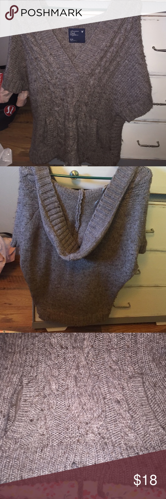 American Eagle Sweater Short Sleeve This is perfect for fall! It's a v-neck sweater but it's short sleeve so it goes perfectly with a plain long sleeve under it. The color is honestly a little confusing, it looks brown but also a little gray. Either way it's so cute and really warm! It has two strings at the bottom you can pull to make the bottom tighter if you want. Also has a hood & a hoodie pocket on it in the front. Get this just in time for fall! Size medium from American Eagle🍁🍃🌾…