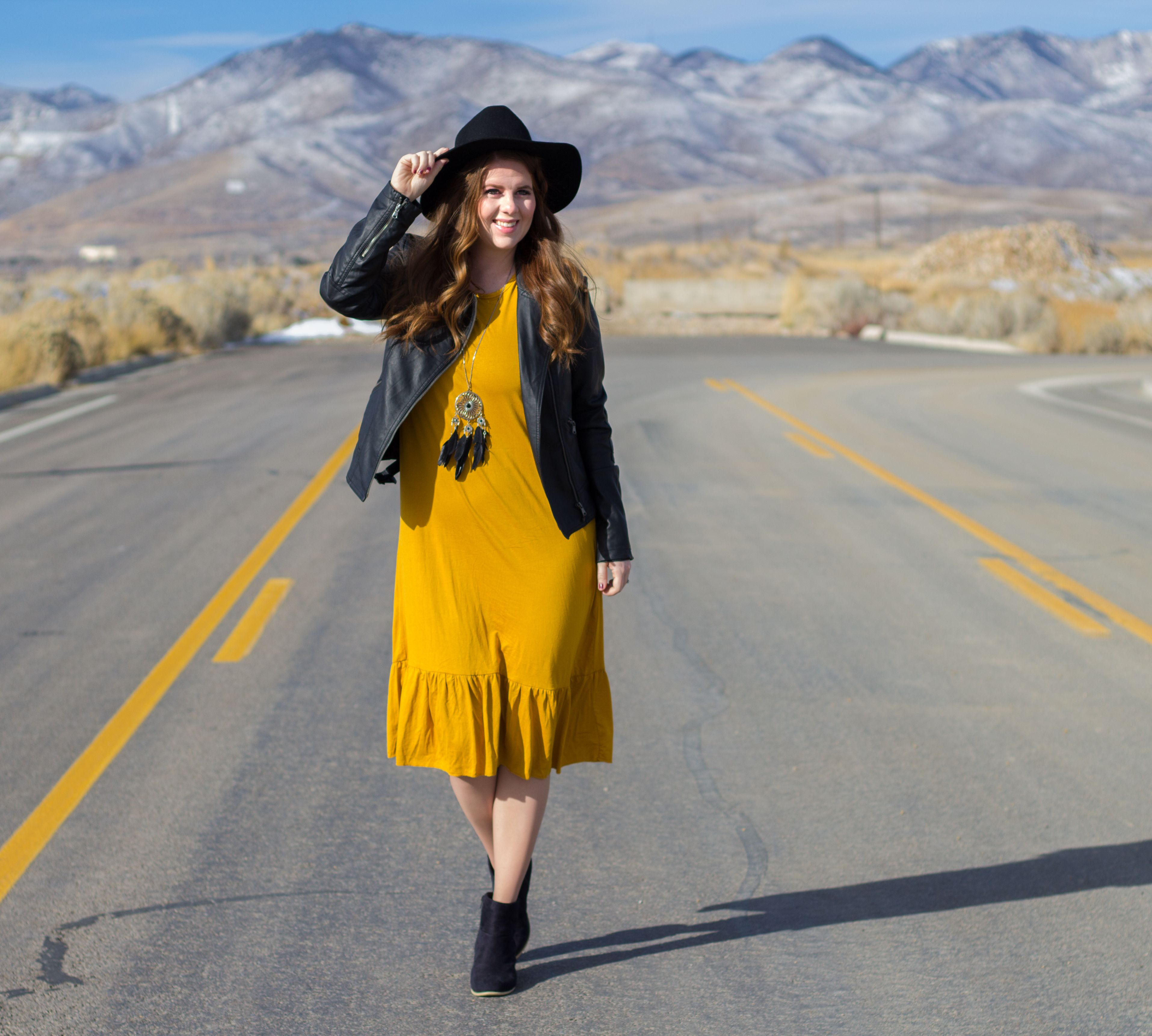 Styling a yellow mustard dress with large ruffles can get tricky. I made sure to pair my outfit with a faux leather jacket and wide brimmed hat to tone down the ruffle. I added a chic pair of black booties and a dream catcher necklace to add to the vibe.
