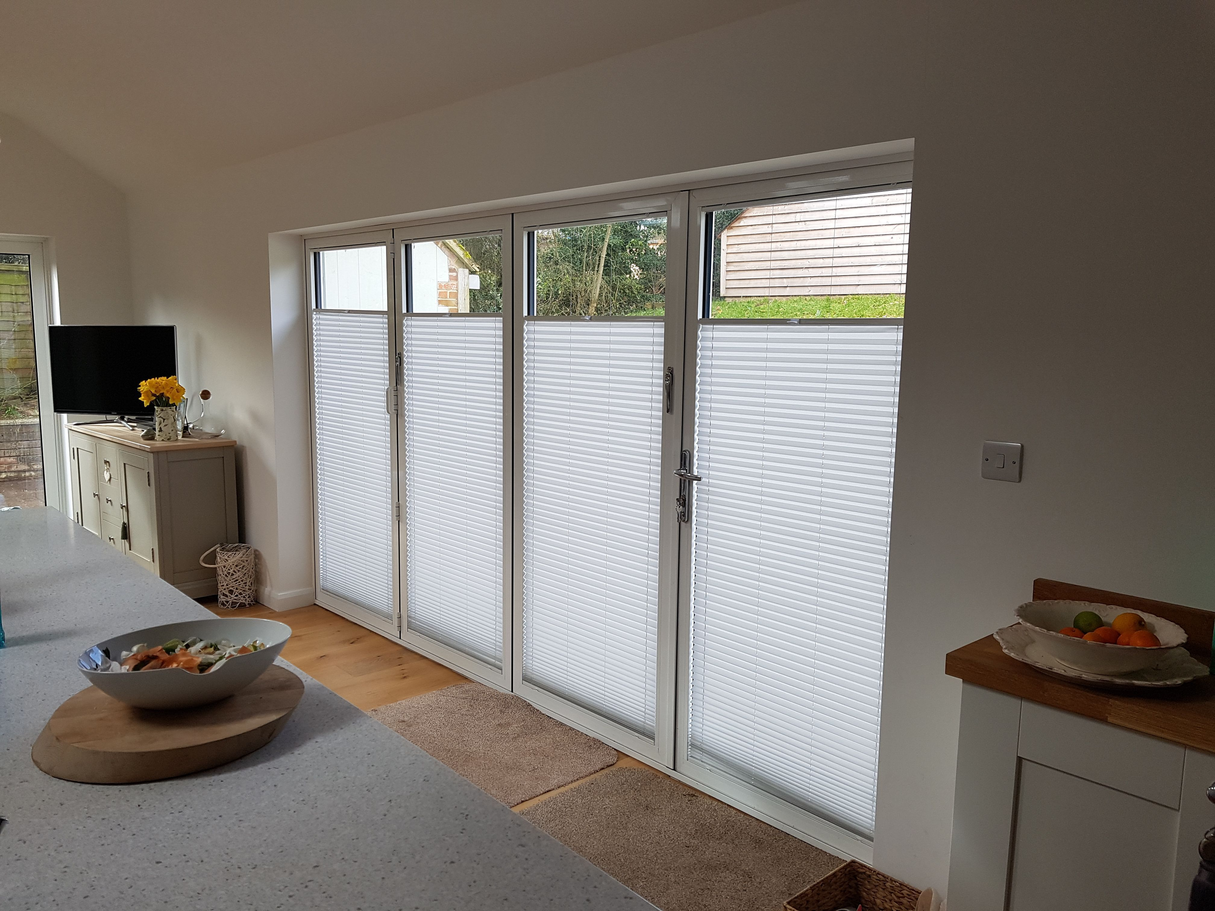 Tension pleated blinds fitted to kitchen bifold doors blinds for