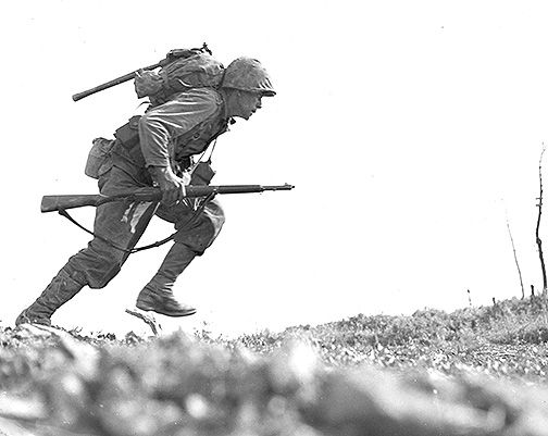 "Okinawa – 10 May 1945. Pfc Paul E. Ison, L 3/5, 1st MarDiv, dashes across open ground in Death Valley. On this date, 3/5 was attached to the 7th Marines.   According to the information supplied to the press with this photo, ""The Marines sustained more than one hundred twenty-five casualties in eight hours while crossing this valley on Okinawa."""