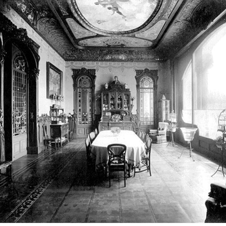 Allure of Art Nouveau.Casa Perez Samanillo. View of the dinning room / now sitting room on the period photo .Casa Perez Samanillo was designed as a single family residence in the Art Nouveau style with gothic inspiration. In the  year of its construction was awarded by City Council Prize for the best building. The interior has preserved much of the original decorative richness. It was made under the direction of the furniture maker Joan Esteva, who used a lot of marquetry. One of the remarkab...: