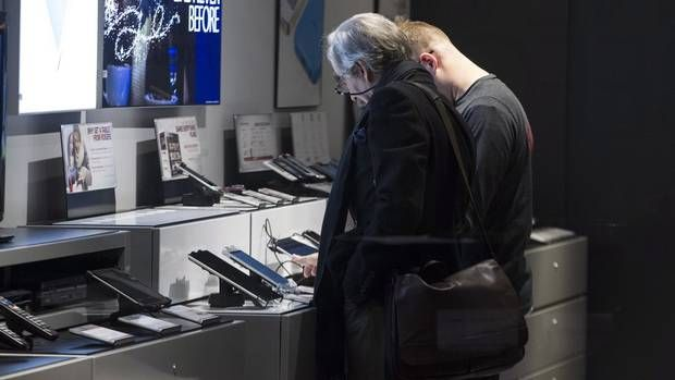 Customers look at electronic devices at the store in the Rogers offices in Toronto. (Chris Young/THE CANADIAN PRESS)