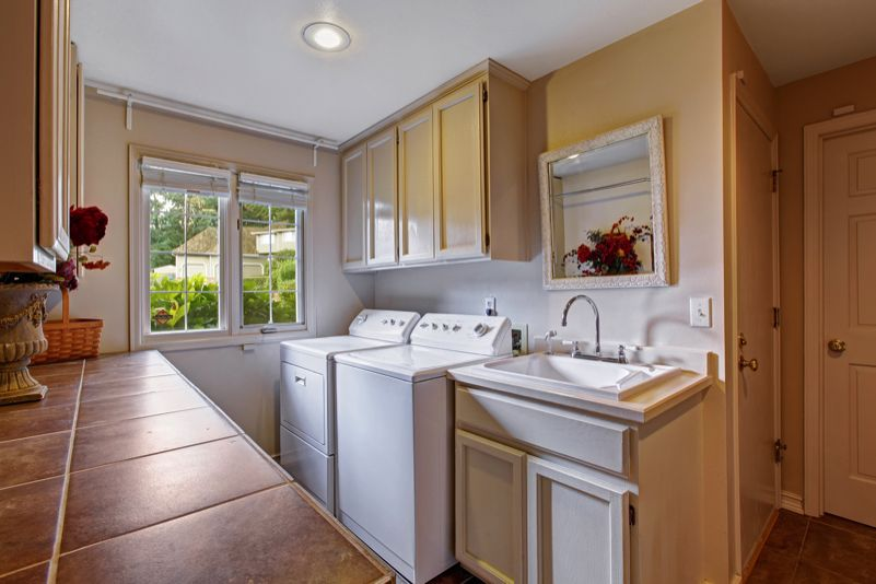 A really nice modern laundry room, the result of a quality makeover. Has a bathroom style sink and cupboards and a tiled bench for folding clothes