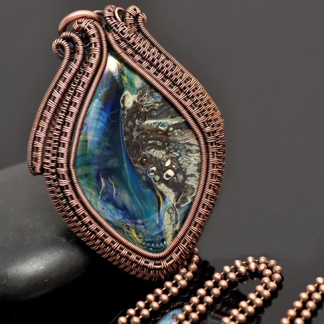 """This wire wrapped and woven copper pendant, measuring just over 5.5cm in length (excluding the bail), features a large handmade artisan glass cabochon by Glaze Ranch Jewelry, with a shower of deep iridescent blue across the surface, and a mottled, mountainous black and green array of color. This lovely glass is set inside hand woven copper bezel, layered in a symmetrical design. This pendant will arrive with a 20"""" copper ball chain.."""