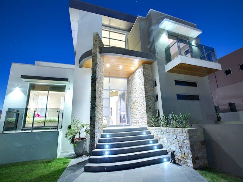 Sandstone modern house exterior with balcony landscaped garden