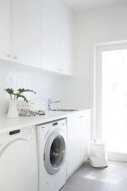 Modern White Laundry Room Features White Cabinets Paired With